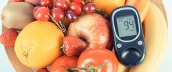Glucometer with result of measurement sugar level and fresh ripe natural fruits and vegetables. Nutritious food containing healthy minerals and vitamins