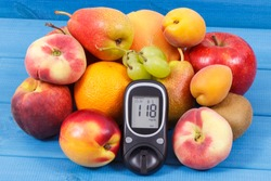 Glucose meter with result sugar level and fruits containing nutritious vitamins and minerals for healthy lifestyles of diabetics
