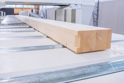 Glued laminated timber lies on a woodworking machine. Selective focus on laminated veneer lumber.