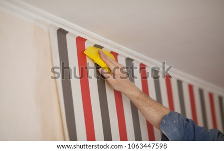 Glueing wallpapers at home. Handyman putting up wallpaper on the wall #1063447598