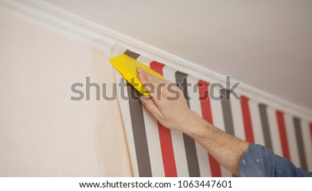 Glueing wallpapers at home. Handyman putting up wallpaper on the wall #1063447601