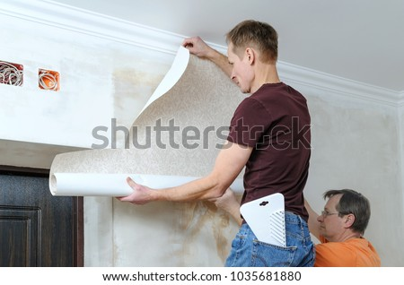 Glueing wallpapers at home. Men are putting up wallpapers on the wall. #1035681880