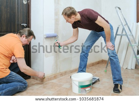 Glueing wallpapers at home. Men are putting wallpaper adhesive on the wall. They are using roller and brush. #1035681874