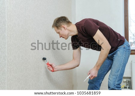Glueing wallpapers at home. The man is using a roller for better adhesion of joints of wallpaper. #1035681859