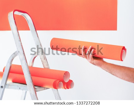 Glueing wallpapers. Living coral home renovation concept. Interior design texture and background in living coral color of the year 2019. Repair, wallpaper sticking.   Wallpaper in male hand.