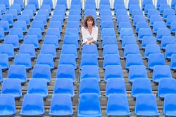 Glum woman sitting in empty rows of blue spectator seating in an auditorium or stadium with a bored expression