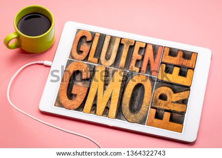 gluten and GMO (genetically modified organism) free banner  - word abstract in vintage on a digital tablet with a cup of coffee #1364322743