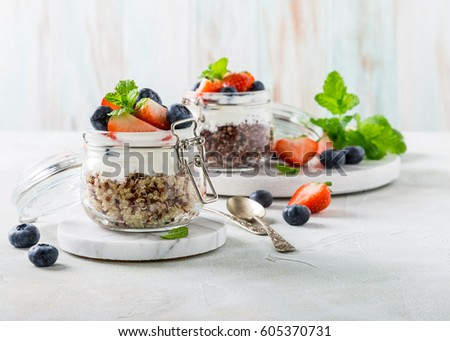 Gluten free breakfast with red quinoa, yogurt and berries in glass jar. Healthy super foods concept with copy space.