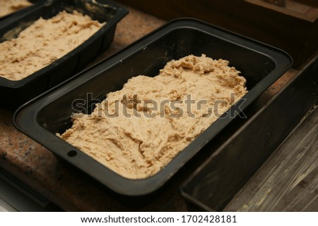 Photo of Gluten free dough inside a baking pan. Bread making concept image.