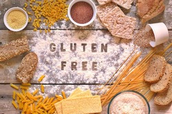 Gluten free flour and cereals millet, quinoa, corn bread, brown buckwheat, rice, bread and pasta with text gluten free in English language with spoon on wooden background,up view