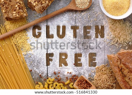 Gluten free flour and cereals millet,quinoa,corn flour polenta,brown buckwheat,basmati rice, bread and pasta with text gluten free in English language with spoon on brown wooden background,up view