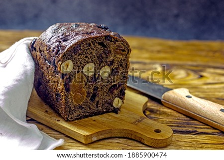 Gluten free fruit bread with raisins, pumpkin and nuts on a wooden table next to a knife and a napkin. The concept of healthy baking without sugar and flour do it yourself.Close-up sectional view Foto d'archivio ©