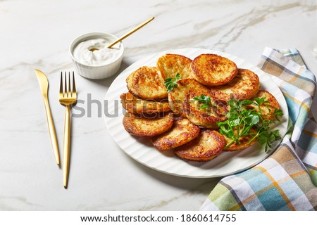 Gluten-free potato pancakes with cottage cheese with garlic, parsley, served with sour cream dip on a plate on a light marble stone background with golden cutlery, top view, close-up Photo stock ©