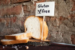 Gluten-free sliced bread on a red brick wall background. Gluten-free sign.