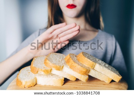Gluten intolerance concept. Young girl refuses to eat white bread. Shallow depth of field. Gesture of refusal