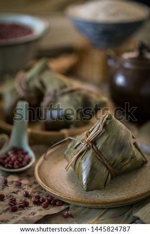 Glutinous rice dumplings with red bean azuki bean wrapped with bamboo leaves with traditional Chinese style setting as background #1445824787