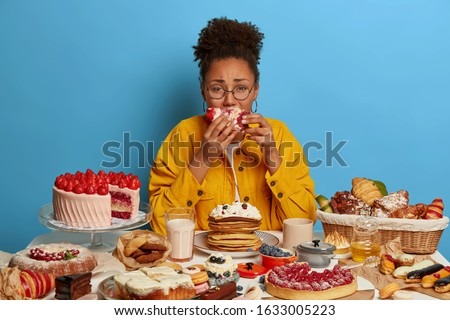 Gluttony and overeating concept. Upset crying ethnic woman eats piece of cake reluctantly, sits at table with many desserts, isolated over blue wall, feels hungry and greedy, wears yellow jacket Photo stock ©