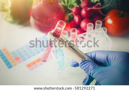 GMO Genetically modified food in lab concept. Analyst in gloves takes test tube.  #581292271