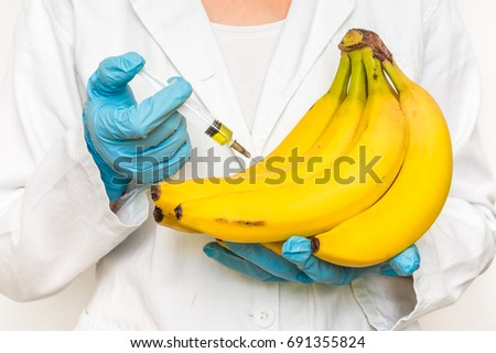 GMO scientist injecting liquid from syringe into bananas - genetically modified food concept #691355824