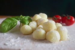 Gnocchi,closeup view,uncooked potato italian pasta with fresh basil and cherry tomatoes,on floured wood board and black background