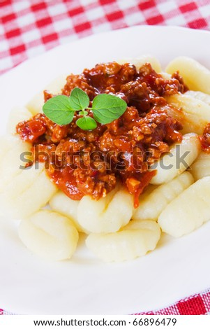 gnocchi di patata, italian potato noodle with sauce bolognese - stock photo