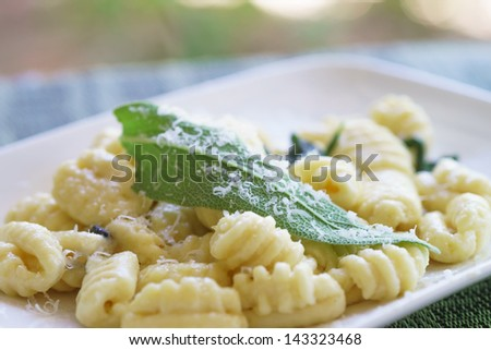 Gnocchi with butter, sage and parmesan.Italian dish. Shallow depth of field. Focus on sage.