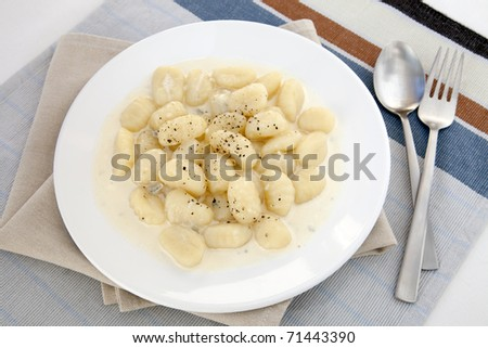 Gnocchi with four cheese wine sauce on with plate with silverware.