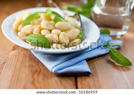 Gnocchi with fresh sage on kitchen table - stock photo