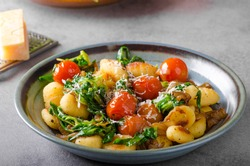 Gnocchi with spinach, garlic and tomatoes, styled photo for advertising