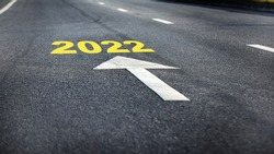 Go ahead to new year 2022 with white arrow on asphalt road surface. Business improvement with challenge concept and keep moving idea
