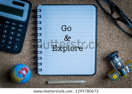 GO AND EXPLORE inscription written on book with globe,eyeglasses, calculator, camera, pencil and vase on wooden background with selective focus and crop fragment. Business and education concept Stock fotó ©