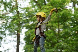 Go Ape Adventure. Adventure climbing high wire park. Child. Happy child boy calling while climbing high tree and ropes. Every childhood matters. Balance beam and rope bridges