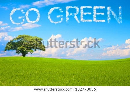 Go Green field and tree on clear blue sky