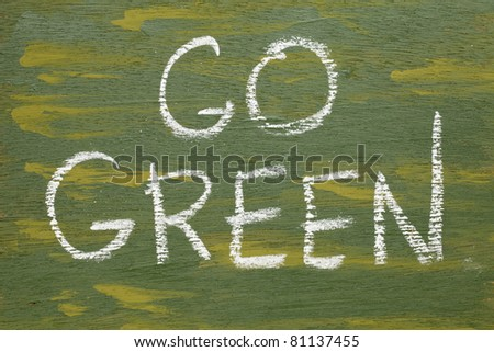 go green sign - white chalk handwriting on plywood board painted green