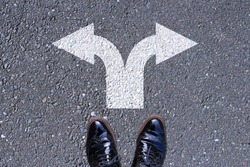 Go left or right. a man standing on the road thinking about choices, turning point, future