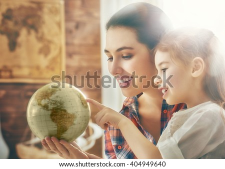 Go on an adventure! Happy family preparing for the journey. Mom and daughter study the globe and choose a route of travel.