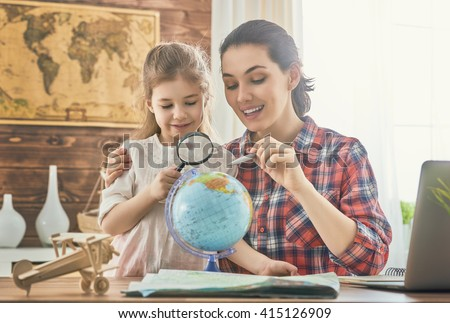 Go on an adventure! Happy family preparing for the journey. Mom and daughter study the map and choose a route of travel.