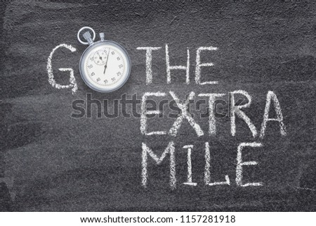 go the extra mile phrase written on chalkboard with vintage stopwatch used instead of O Foto stock ©
