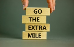 Go the extra mile symbol. Wooden blocks with words 'Go the extra mile'. Male hand. Beautiful grey background. Business and go the extra mile concept. Copy space.