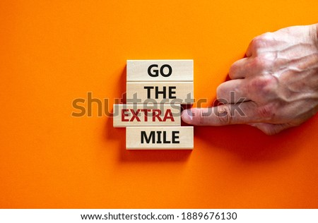 Go the extra mile symbol. Wooden blocks with words 'Go the extra mile'. Male hand. Beautiful orange background. Business and go the extra mile concept. Copy space. ストックフォト ©