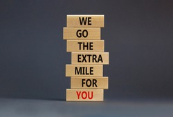 Go the extra mile symbol. Wooden blocks with words 'We go the extra mile for you'. Beautiful grey background. Business, motivational and go the extra mile concept. Copy space.