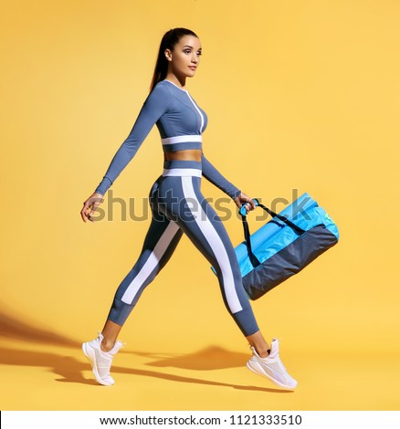 Go to training. Sporty woman with bag on yellow background. Dynamic movement. Side view. Sport and healthy lifestyle