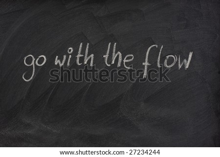 go with the flow phrase handwritten with white chalk on blackboard with erase smudge patterns