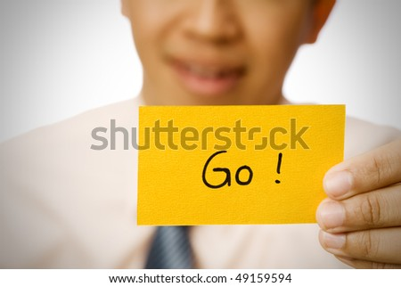 Go word on yellow card holding by businessman.