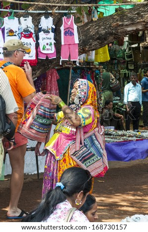 GOA, INDIA - FEBRUARY 20, 2013: Woman in authentic clothing offering people her goods on the Mandrem market on February 20, 2013 in Goa, India