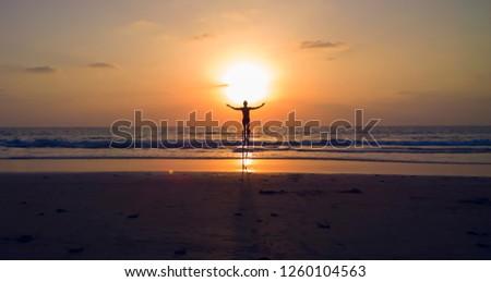 Goa, India. Man dancing on the stilts. Sunset on the beach. #1260104563