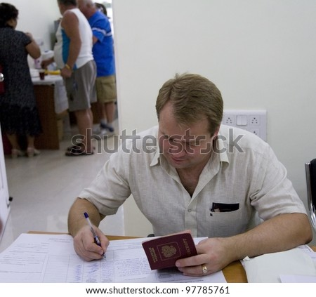 GOA, INDIA - MARCH 4: Russian clerk  fill list  of voted people during election of Russian president on March 4, 2012 in Goa, India.