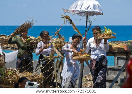 GOA LAWAH, INDONESIA - SEPTEMBER 1: Unidentified persons carry offers and say prayers to the ocean, in Goa lawah, Bali, Indonesia, on September 1, 2009. The ceremony took place  during a cremation