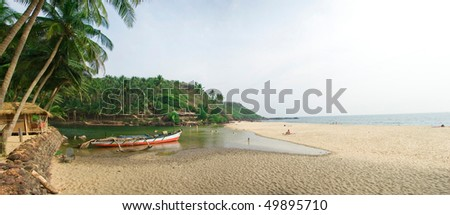 Goa's beach with river at the left sight and sea at the right sight. Panorama from the tree photos