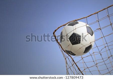 Goal. a soccer ball in a net.